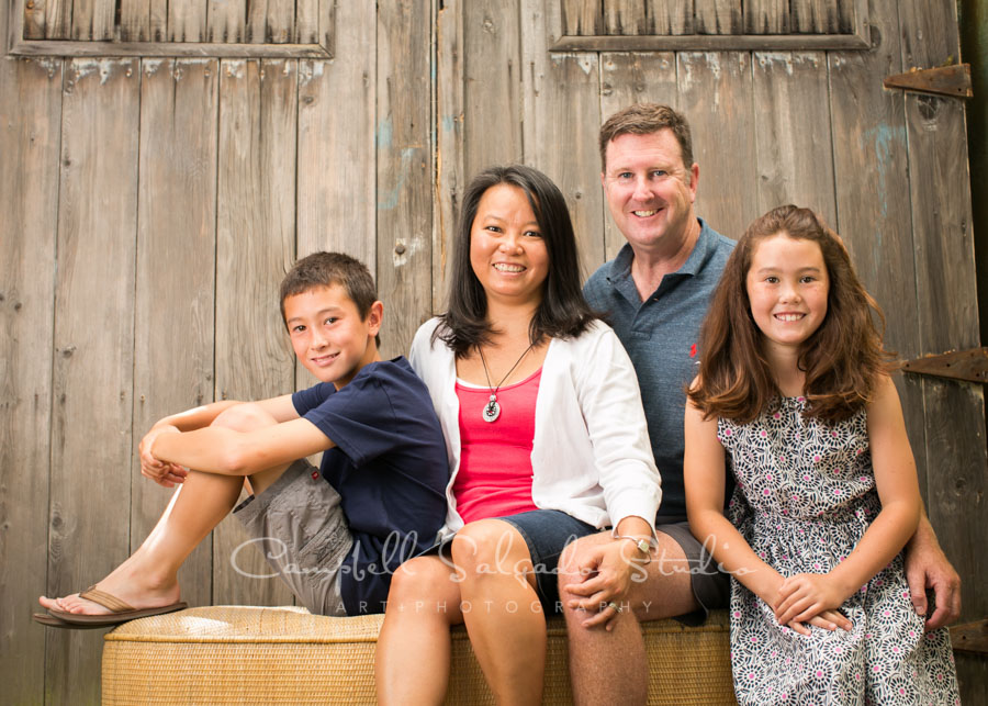 Portrait of family on old barn doors background by family photographers at Campbell Salgado Studio in Portland, Oregon.