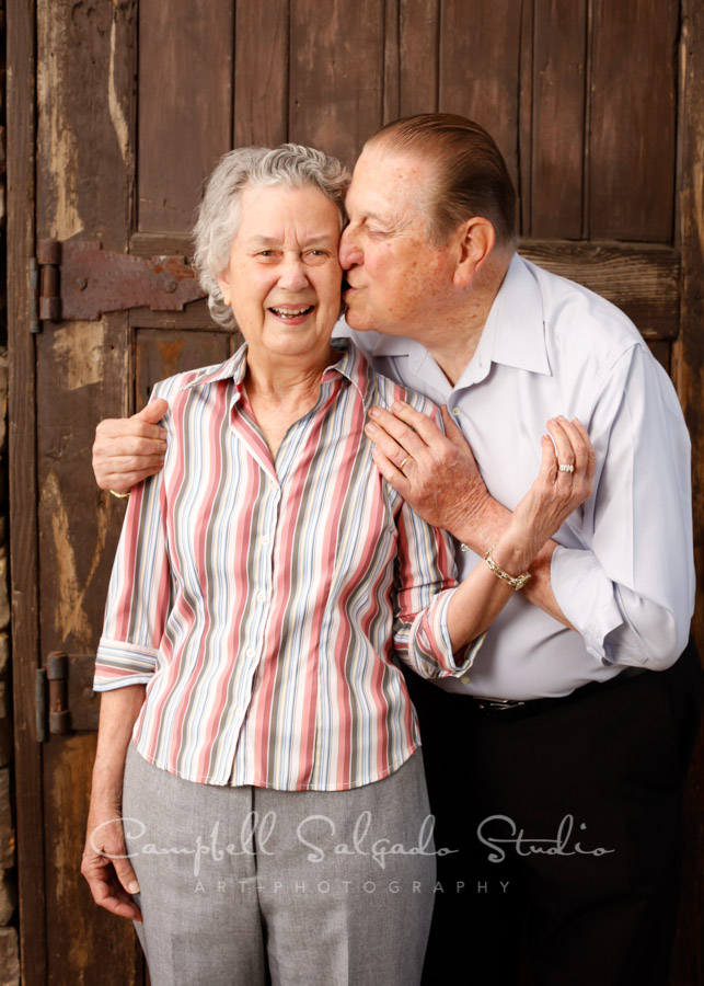 Portrait of couple on rustic door background by couples photographers at Campbell Salgado Studio in Portland, Oregon.