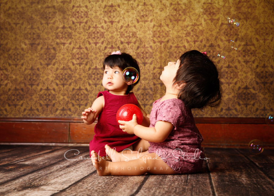 Portrait of twins on amber light background by family photographers at Campbell Salgado Studio in Portland, Oregon.