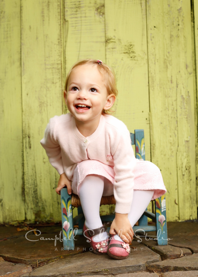 Portrait of child on lime fenceboards background by child photographers at Campbell Salgado Studio in Portland, Oregon.