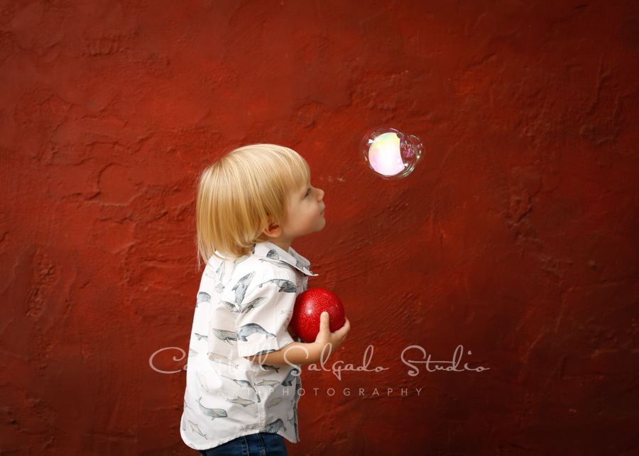 Portrait of boy on red stucco background by family photographers at Campbell Salgado Studio in Portland, Oregon.