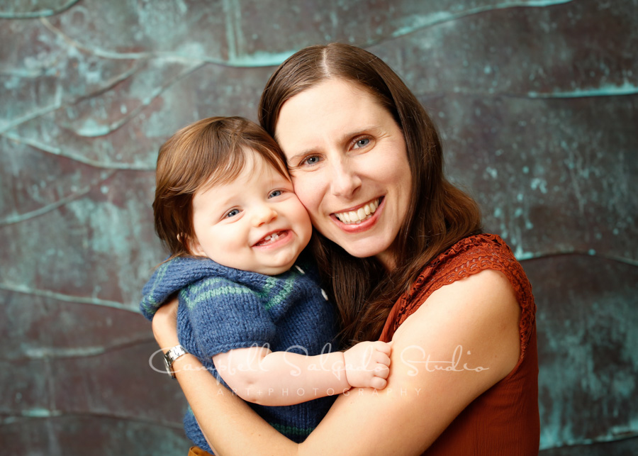 Portrait of mother and child on ocean wave background by family photographers at Campbell Salgado Studio in Portland, Oregon.