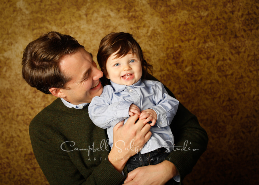 Portrait of father and child on amber light background by family photographers at Campbell Salgado Studio in Portland, Oregon.