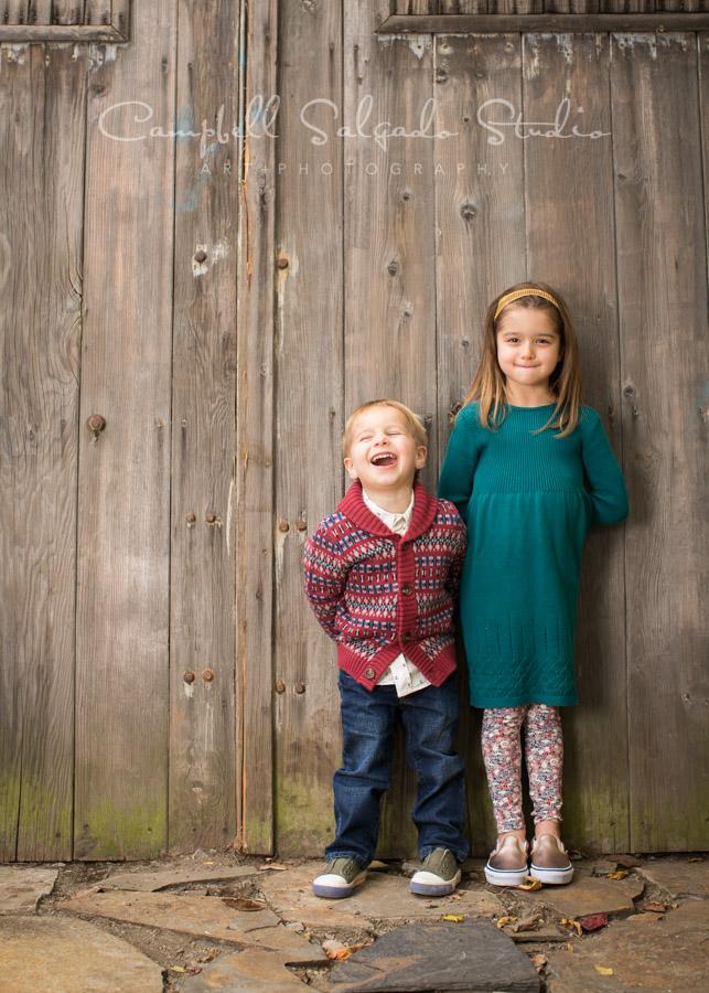 Portrait of children on barn doors background by child photographers at Campbell Salgado Studio in Portland, Oregon.