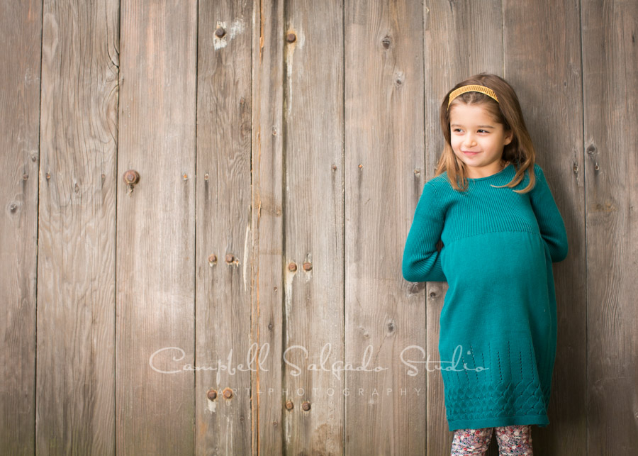 Portrait of girl on old doors background by child photographers at Campbell Salgado Studio in Portland, Oregon.