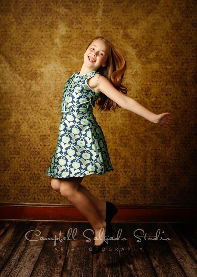 Portrait of girl on plum amber light background by child photographers at Campbell Salgado Studio in Portland, Oregon.