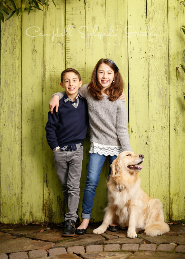 Portrait of kids on lime fence boards background by family photographers at Campbell Salgado Studio in Portland, Oregon.