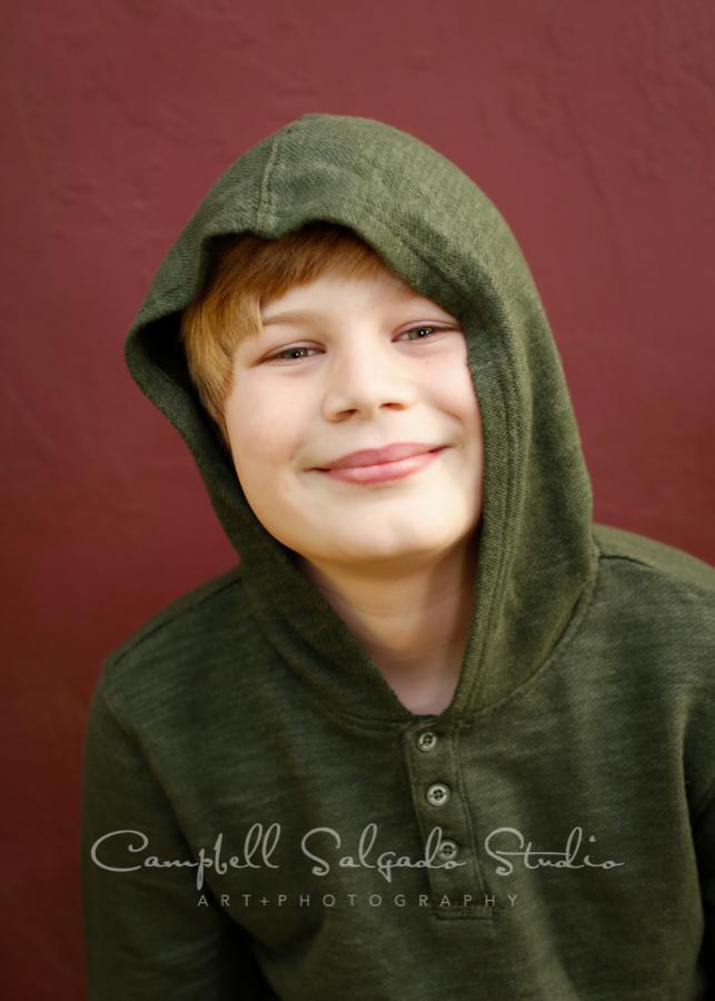 Portrait of boy on plum stucco background by child photographers Campbell Salgado Studio in Portland, Oregon.
