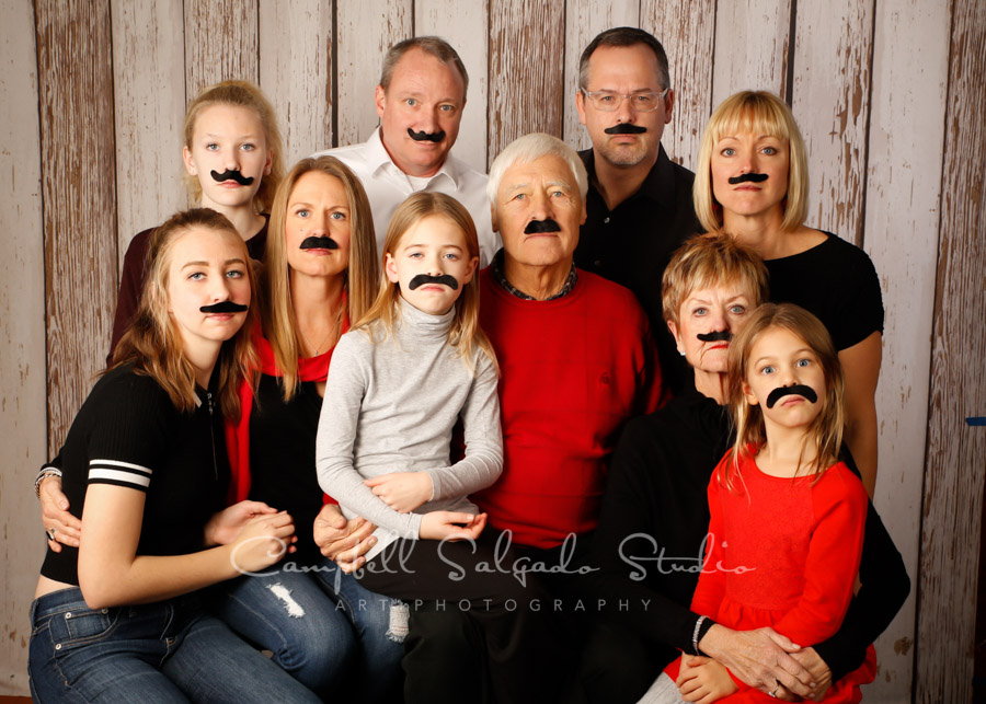 Portrait of multi-generational family on white fenceboards background by family photographers at Campbell Salgado Studio in Portland, Oregon.