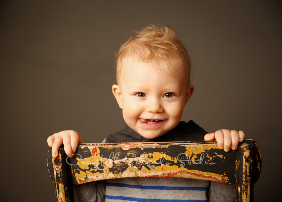 Portrait of child on gray background by childrens photographers at Campbell Salgado Studio in Portland, Oregon.