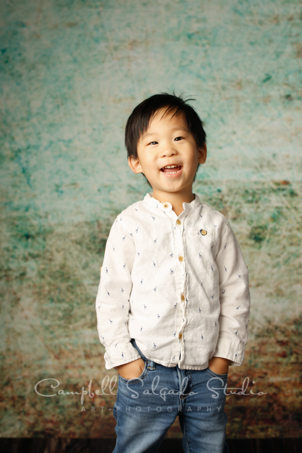Portrait of toddler on weathered green background by child photographers at Campbell Salgado Studio in Portland, Oregon.