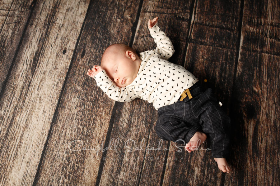 Portrait of baby on wood floor background by baby photographers at Campbell Salgado Studio in Portland, Oregon.
