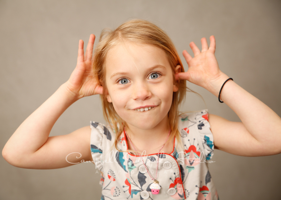 Portrait of girl on modern grey background by child photographers at Campbell Salgado Studio in Portland, Oregon.