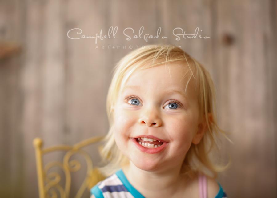 Portrait of girl on barn doors background by children's photographers at Campbell Salgado Studio in Portland, Oregon.
