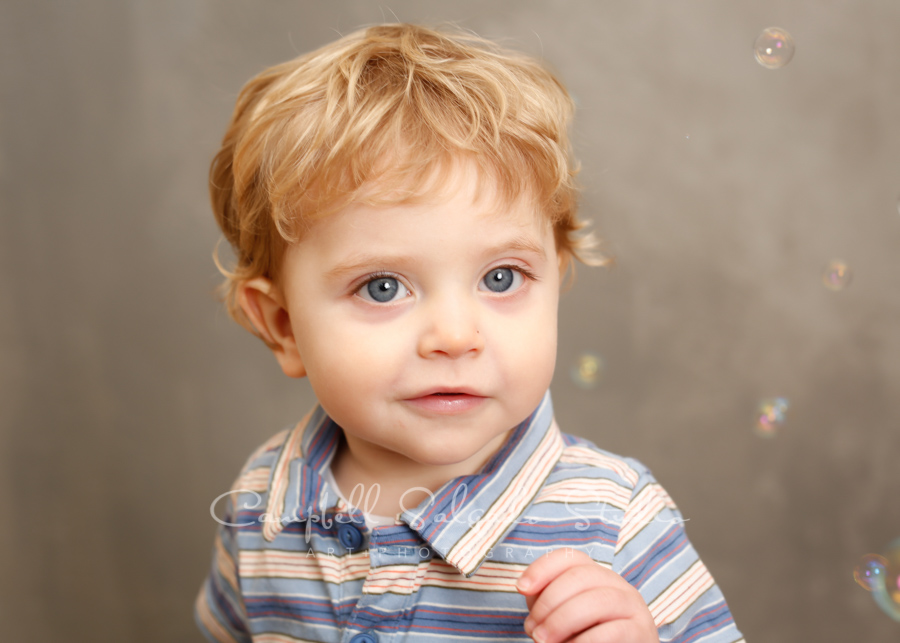 Portrait of toddler on modern gray background by child photographers at Campbell Salgado Studio in Portland, Oregon.