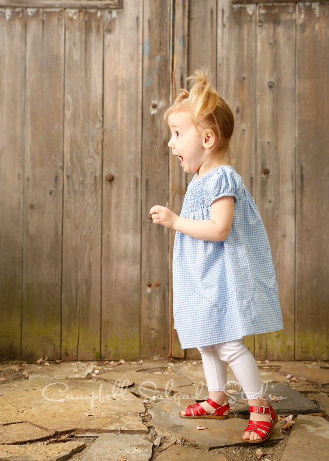Portrait of toddler on barn doors background by children's photographers at Campbell Salgado Studio in Portland, Oregon.