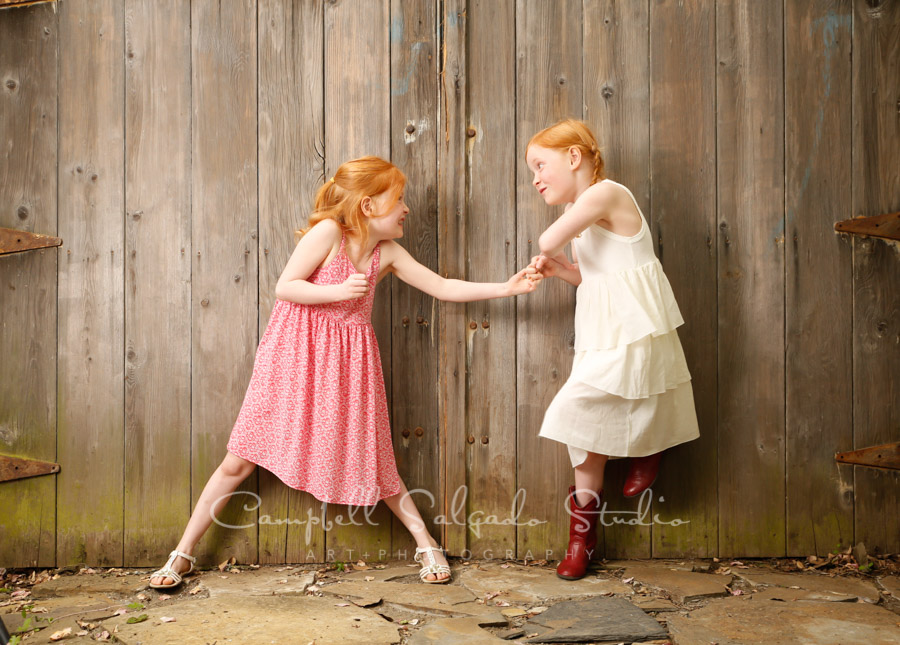 Portrait of twins on barn doors background by children's photographers at Campbell Salgado Studio in Portland, Oregon.