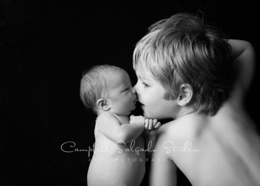 Portrait of siblings on black background by newborn photographers at Campbell Salgado Studio in Portland, Oregon.