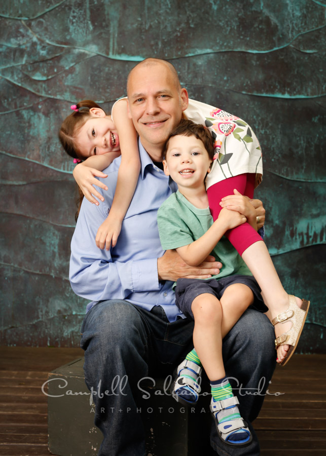 Portrait of dad and kids on ocean weave background by family photographers at Campbell Salgado Studio in Portland, Oregon.