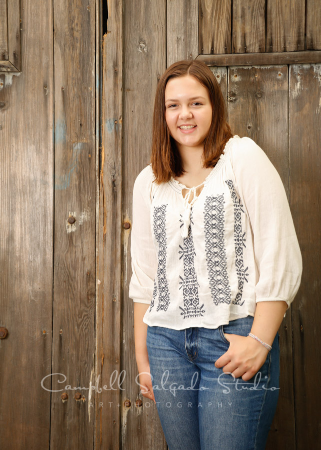 Portrait of teen on barn doors boards background by teen photographers at Campbell Salgado Studio in Portland, Oregon.