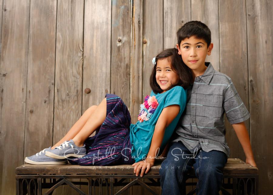 Portrait of kids on barn doors background by child photographers at Campbell Salgado Studio in Portland, Oregon.
