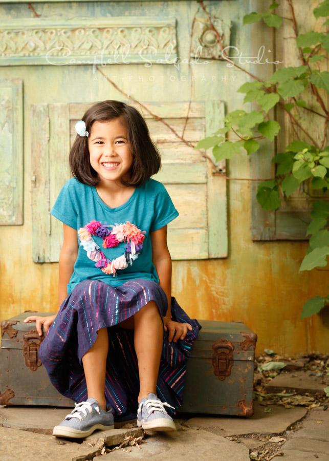 Portrait of girl on vintage green doors background by children's photographers at Campbell Salgado Studio in Portland, Oregon.