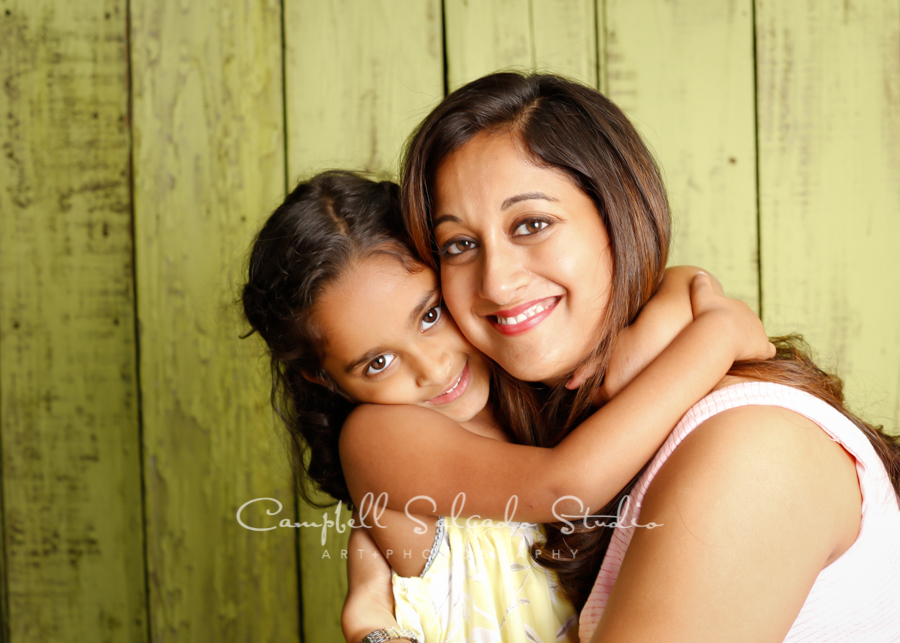 Portrait of mother and daughter on lime fenceboards background by family photographers at Campbell Salgado Studio in Portland, Oregon.