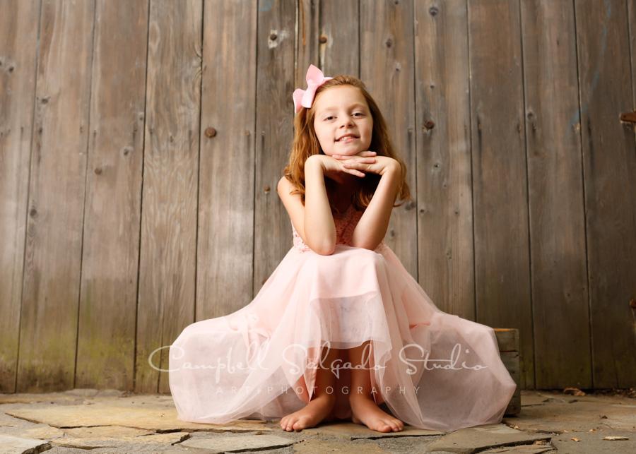 Portrait of girl on barn doors background by child photographers at Campbell Salgado Studio in Portland, Oregon.