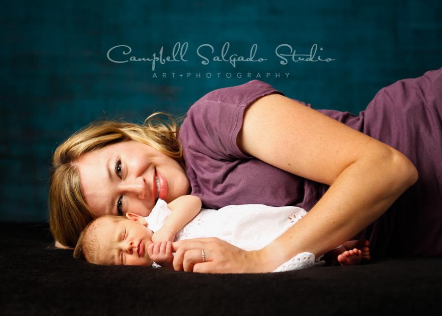 Portrait of newborn and mother on deep ocean background by newborn photographers at Campbell Salgado Studio in Portland, Oregon.