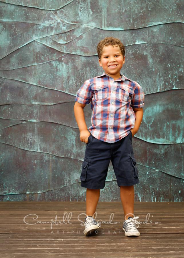 Portrait of kid on ocean weave background by child photographers at Campbell Salgado Studio in Portland, Oregon.