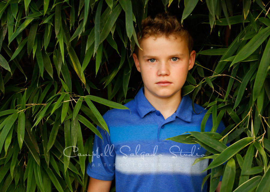 Portrait of kid on bamboo background by child photographers at Campbell Salgado Studio in Portland, Oregon.