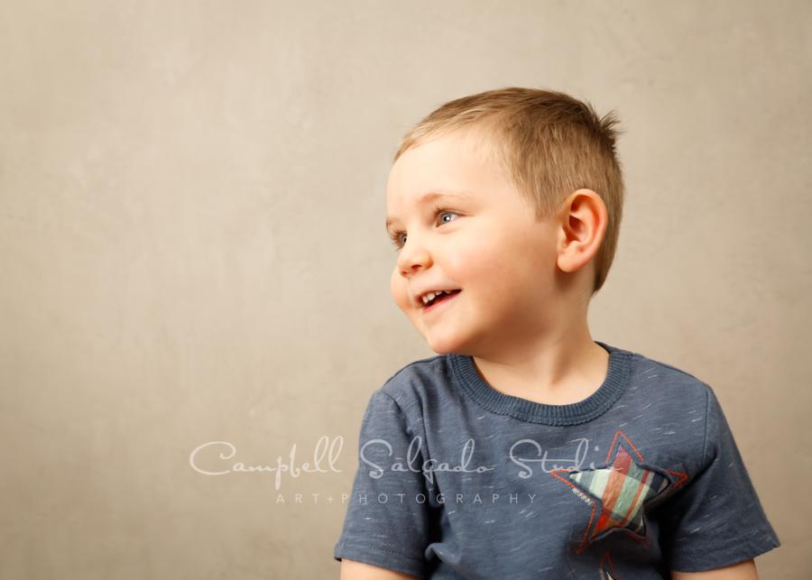 Portrait of child on modern grey background by child photographers at Campbell Salgado Studio in Portland, Oregon.