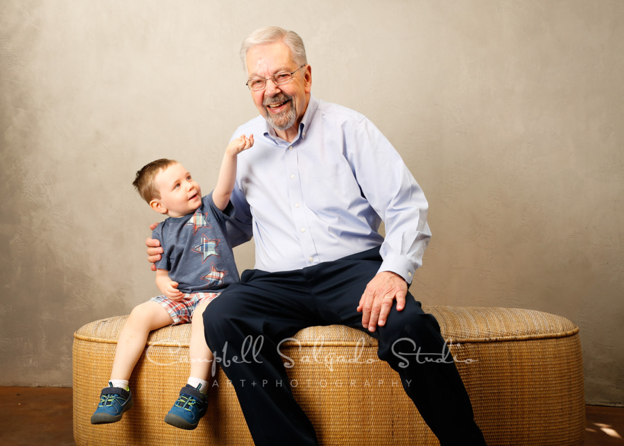 Portrait of grandfather and grandson on modern grey background by family photographers at Campbell Salgado Studio in Portland, Oregon.
