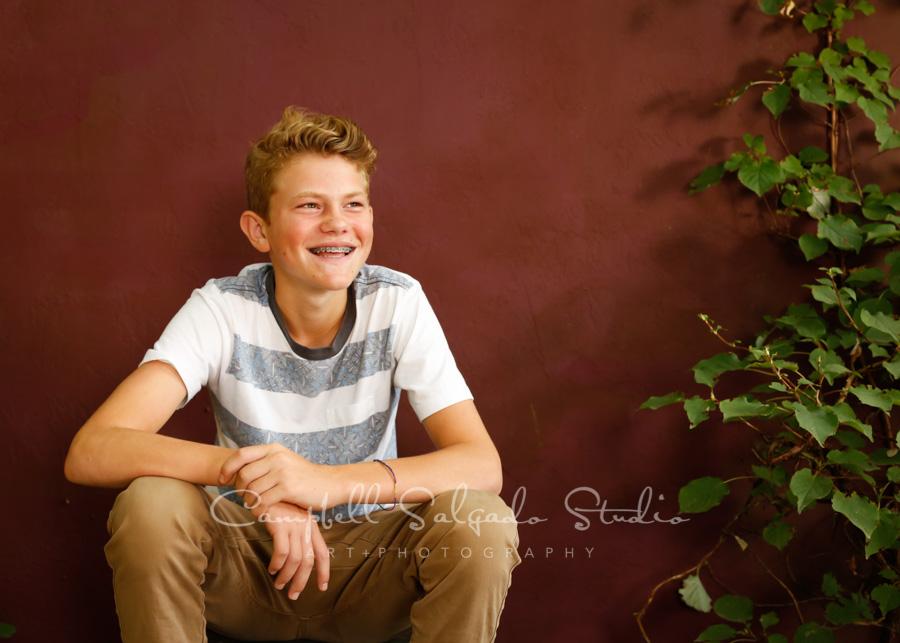 Portrait of teen on plum stucco background by teen photographers at Campbell Salgado Studio in Portland, Oregon.