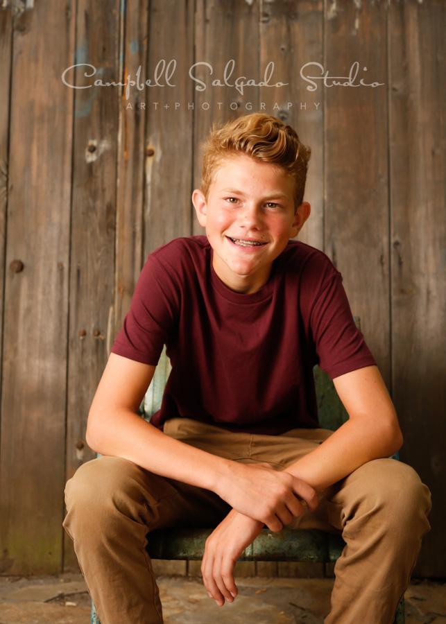 Portrait of teen on barn doors background by teen photographers at Campbell Salgado Studio in Portland, Oregon.