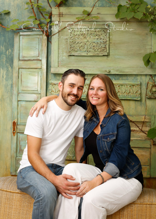 Portrait of couple on vintage green doors background by couple's photographers at Campbell Salgado Studio in Portland, Oregon.