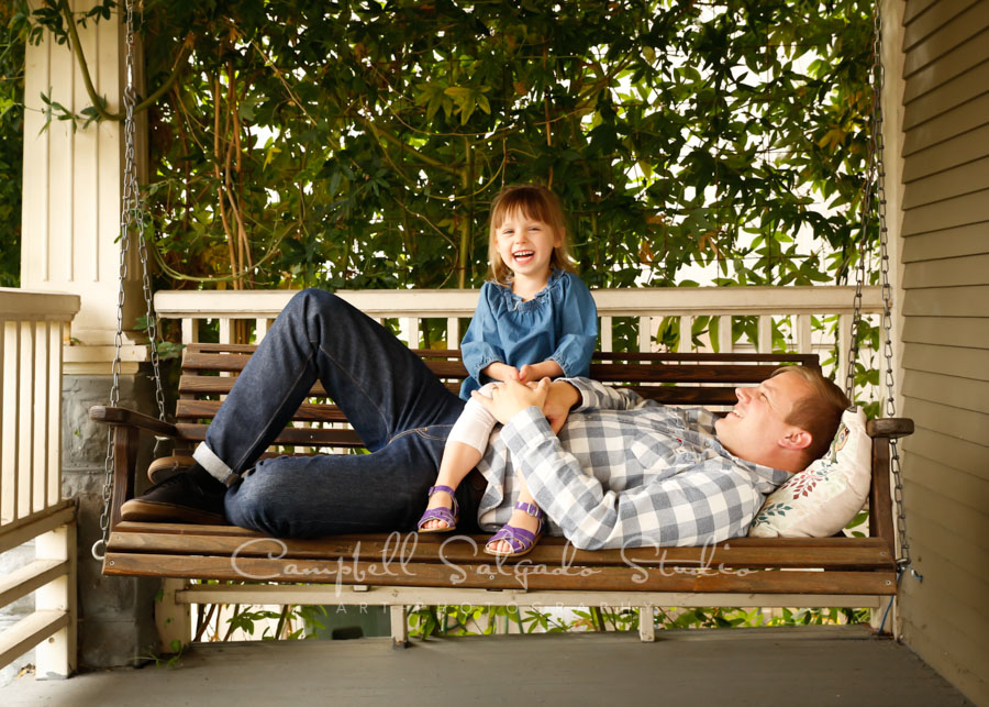 Portrait of father and daughter on porch swing background by family photographers at Campbell Salgado Studio in Portland, Oregon.
