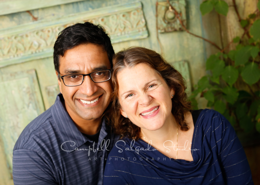 Portrait of couple on vintage green doors background by couples photographers at Campbell Salgado Studio in Portland, Oregon.