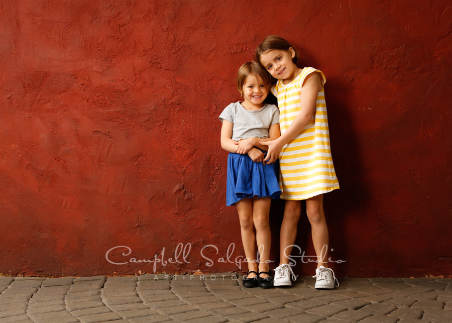 Portrait of sisters on red stucco background by child photographers at Campbell Salgado Studio in Portland, Oregon.