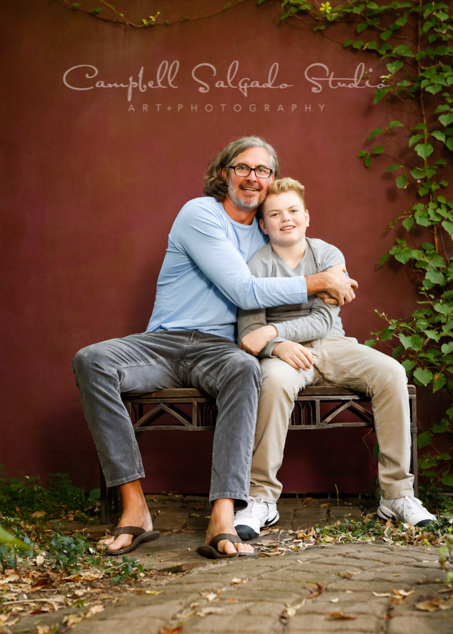 Portrait of father and son on plum stucco background by family photographers at Campbell Salgado Studio in Portland, Oregon.