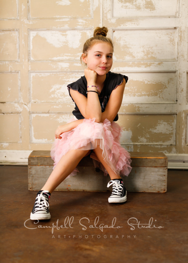 Portrait of girl on antique white doors background by child photographers at Campbell Salgado Studio in Portland, Oregon.