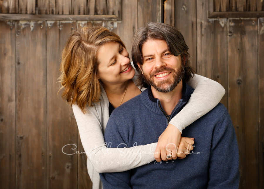 Portrait of couple on barn doors background by couples photographers at Campbell Salgado Studio in Portland, Oregon.