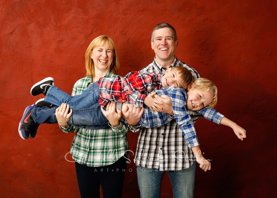 Portrait of family on red stucco background by family photographer at Campbell Salgado Studio in Portland, Oregon