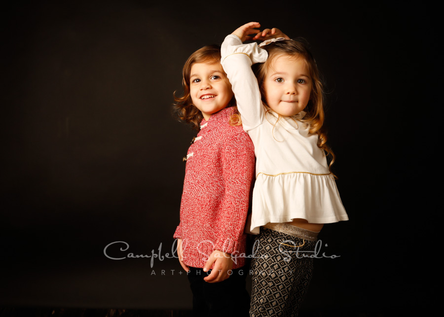 Portrait of twin toddlers on black background by child photographers at Campbell Salgado Studio in Portland, Oregon.