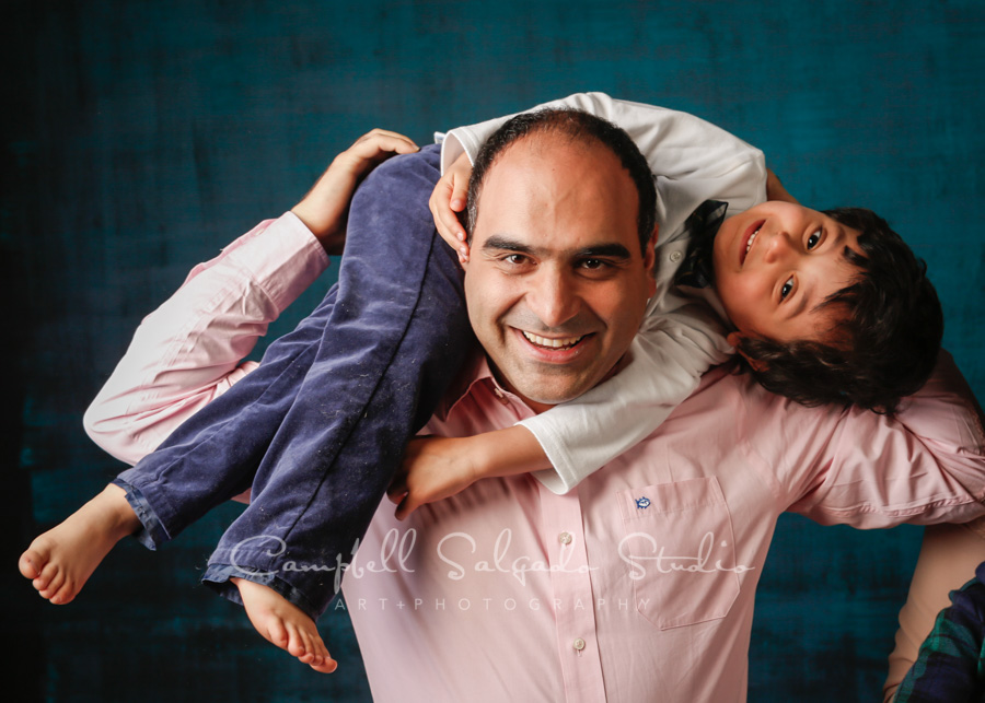 Portrait of father and son on deep ocean background by family photographers at Campbell Salgado Studio in Portland, Oregon.