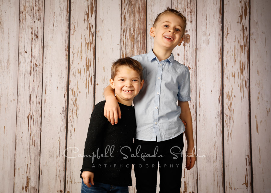 Portrait of children on white fenceboards background by child photographers at Campbell Salgado Studio in Portland, Oregon.