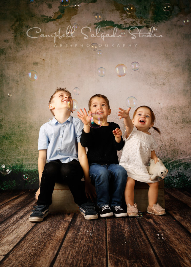 Portrait of children on weathered green background by child photographers at Campbell Salgado Studio in Portland, Oregon.