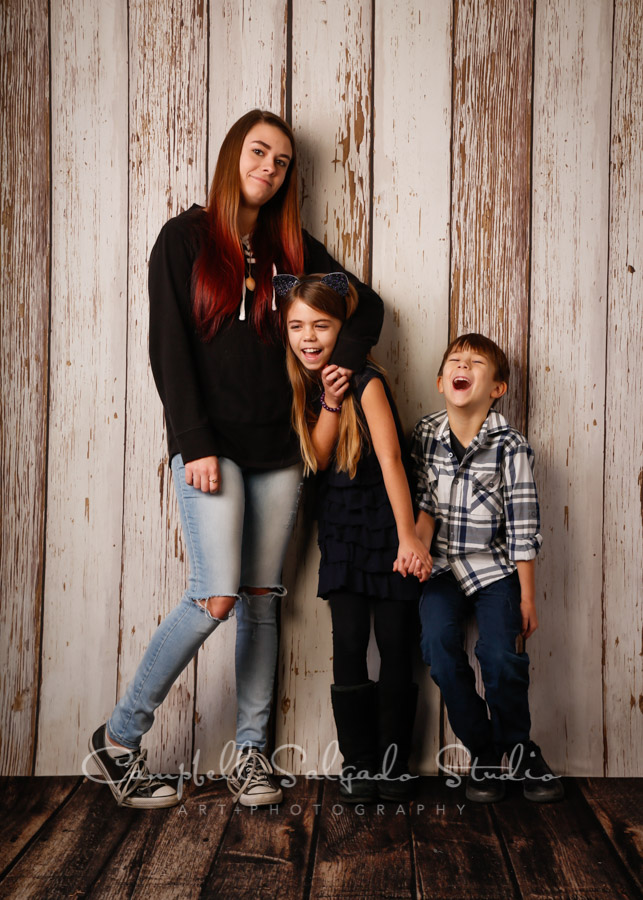 Portrait of siblings on white fenceboards background by child photographers at Campbell Salgado Studio in Portland, Oregon.