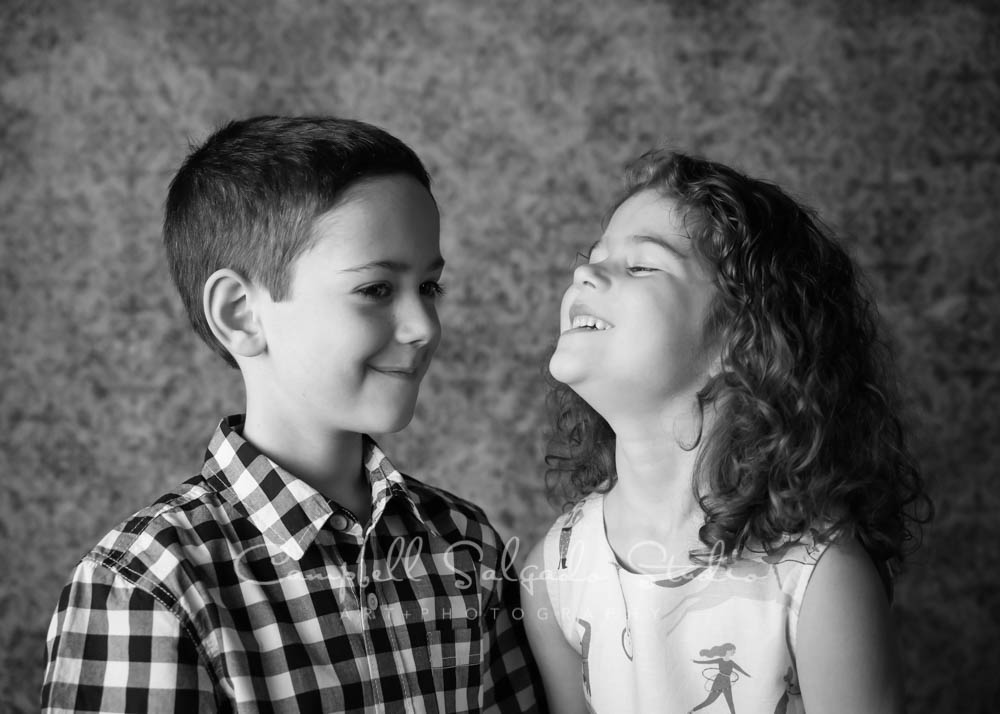 Black and white portrait of children on amber light background by children's photographer at Campbell Salgado Studio in Portland, Oregon.