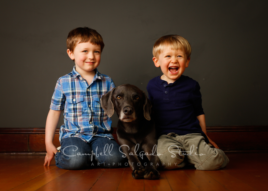 Portrait of children and dog on grey background by pet photographers at Campbell Salgado Studio in Portland, Oregon.